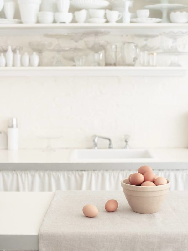 Basket of brown eggs on countertop with bowls on shelf in white