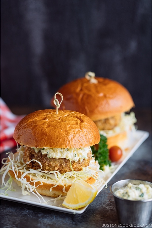 Menchi Katsu Sandwich is a ground meat patty coated with crispy panko and deep fried into golden brown. It is then topped with thinly sliced cabbage and homemade tartar sauce, and sandwiched in soft brioche buns.