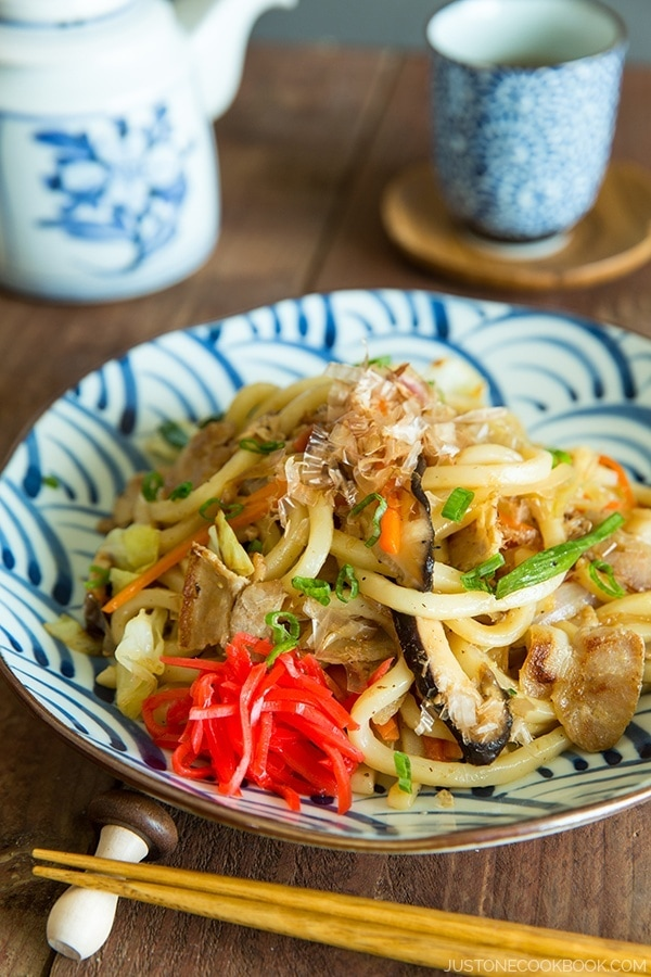Yaki Udon with red ginger pickles on a plate.