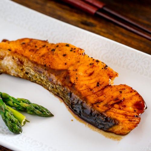 A white plate containing teriyaki salmon with glaze and asparagus.