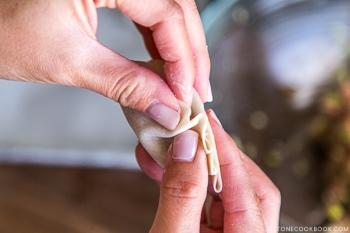 fingers making gyoza with gyoza wrapper