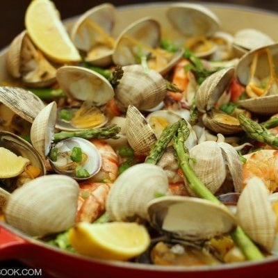 Paella with chicken thighs, squid, shrimps, manila clams, and asparagus in a pot.
