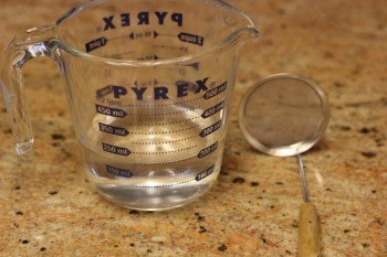 water in a measuring cup next to a mesh skimmer on granite countertop