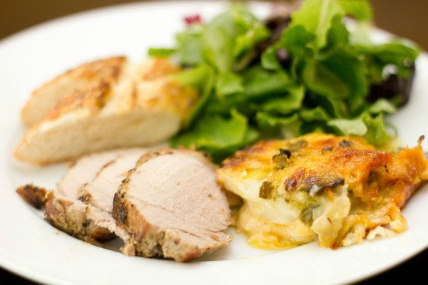 Potato-Leek Gratin, chicken, and salad on a plate.