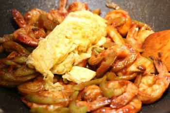 egg poured into shrimp stir fry in a metal pan