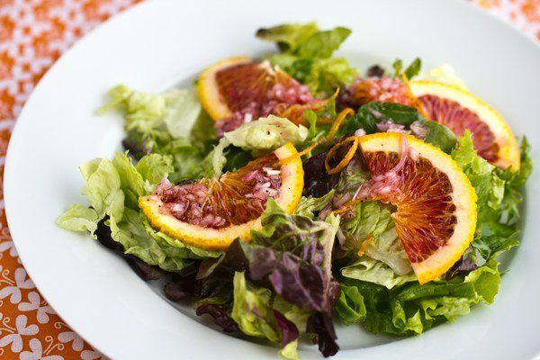 Green Salad with Blood Orange Vinaigrette on a white plate.