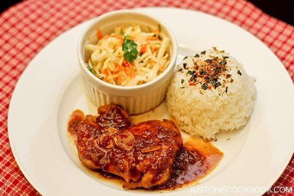 Chicken with Garlic Onion Sauce, white rice, and Asian Coleslaw on a white plate.
