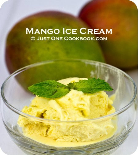 Mango Ice Cream in a glass cup and mangoes on a side.