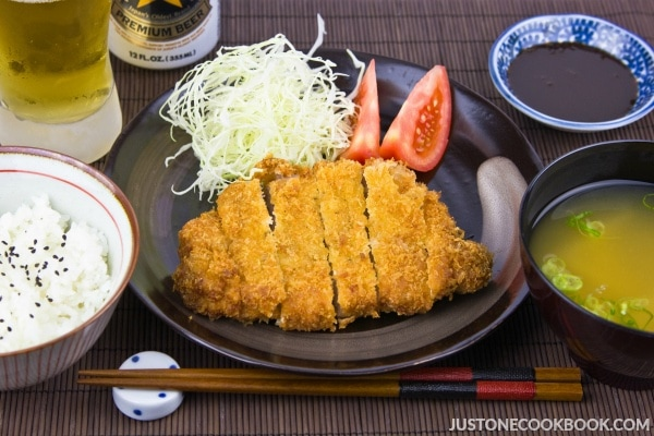 Tonkatsu, salad, rice and miso soup on a table.