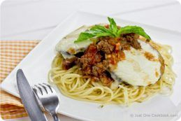 Eggplant Parmesan with Meat Sauce over spaghetti on a plate.