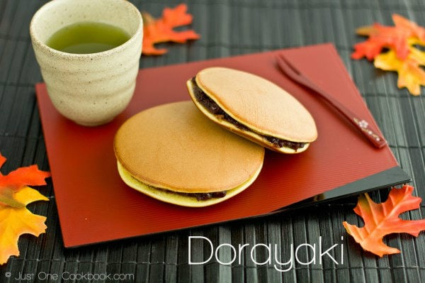 Dorayaki on a red plate with a cup of green tea.