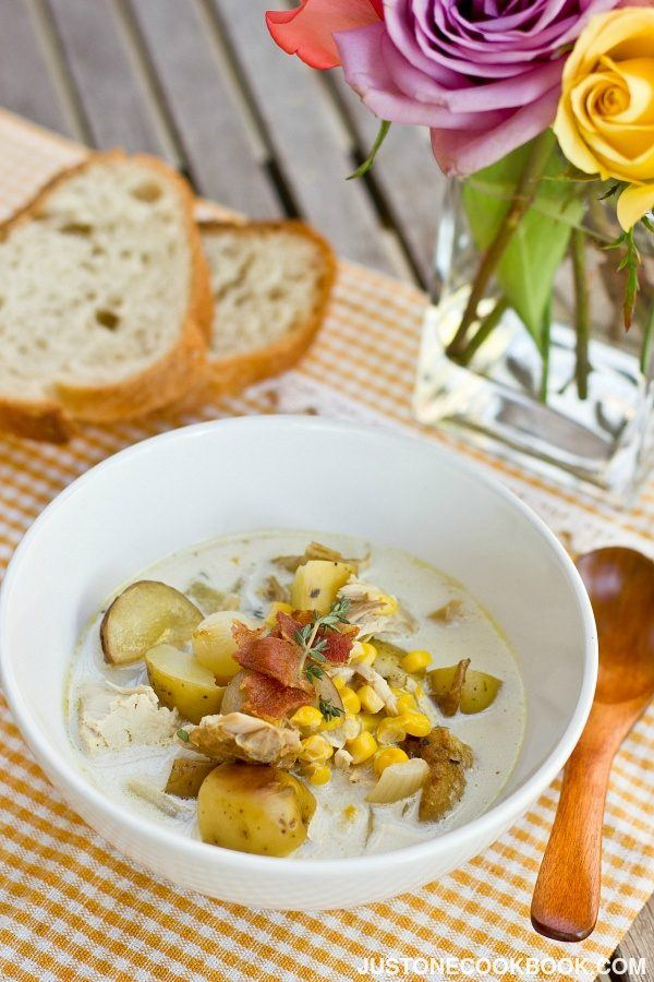 Chicken Corn Chowder in a white soup bowl and sliced breads on the table.