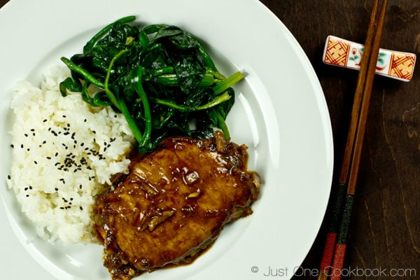 Asian Pork Chop with white rice and sauteed spinach on a white plate.