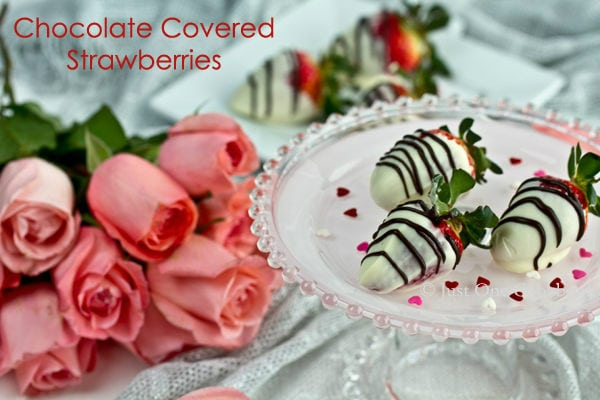 Chocolate Covered Strawberries on a cake stand and pink roses.