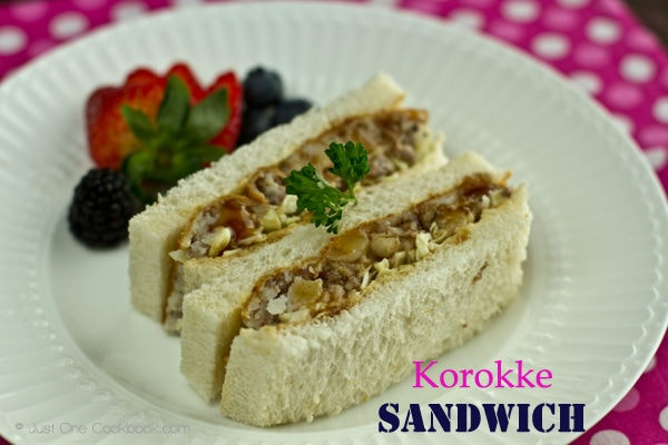 Mom's Korokke sandwiches with berries on a white plate.