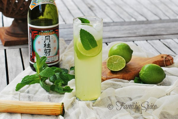 Sake Mojito in a glass and ingredients on a side.