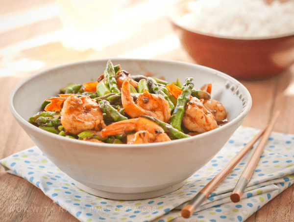 Stir Fried Shrimp & Asparagus in a bowl and steamed rice on a side.
