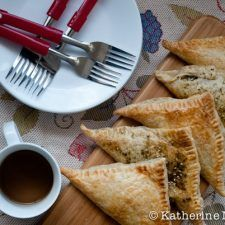 Spinach and Feta Turnovers on a table with plates, forks, and a cup of tea.