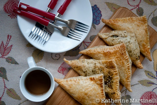Spinach and Feta Turnovers on a cutting board with a cup of tea, and plates and forks on a table.