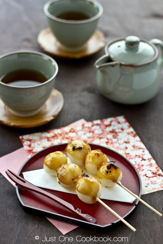 Mitarashi Dango on a small plate and cup of tea.