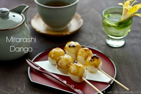 Mitarashi Dango on a plate and a cup of tea on a table.