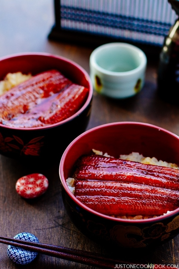 A classic Japanese dish Unadon in a Japanese lacquer bowl containing steamed rice and grilled eel fillet caramelized in sweet soy-based sauce.