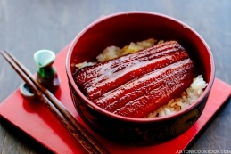A classic Japanese dish Unadon in a Japanese lacquer bowl containing steamed rice, grilled eel fillet caramelized in sweet soy-based sauce.