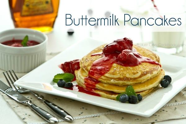Buttermilk Pancakes with strawberry sauce on a white plate.
