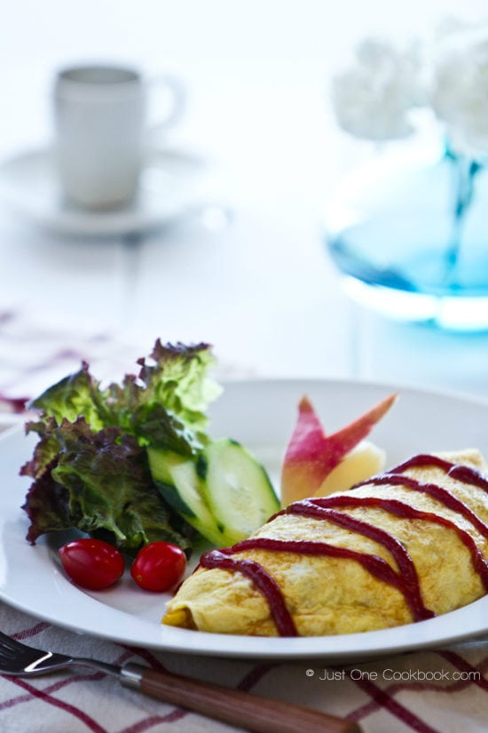Omurice and salad on a white plate.