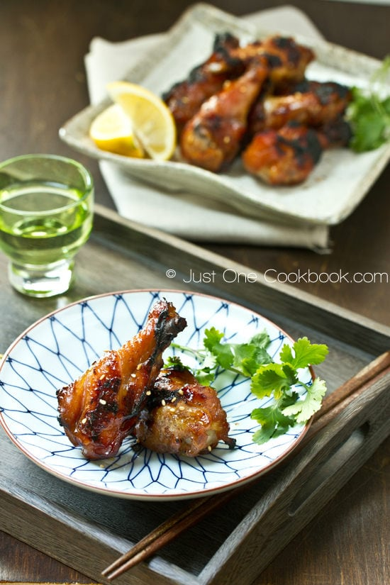 BBQ Chicken Wings on a plate and glass of drink on a wooden tray.