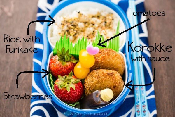 Korokke Bento with rice, tomatoes and strawberries.