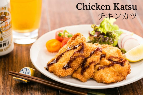 Chicken Katsu with salad on a plate and a glass of beer on a wooden table.