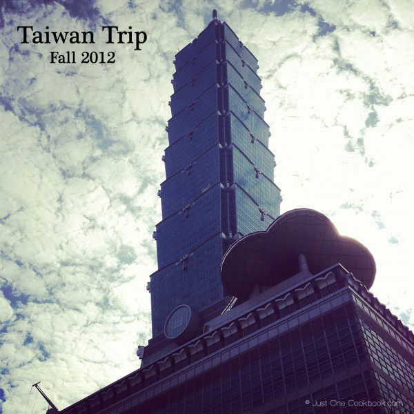 view of taipei 101 from the bottom with clouds in the background