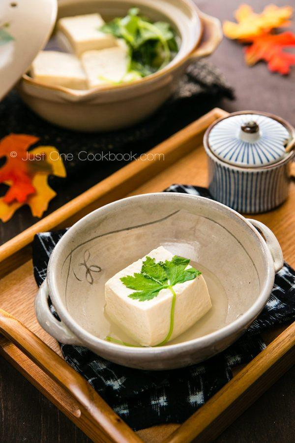 Hot Tofu in a b big pot and a mall bowl on a wooden table.