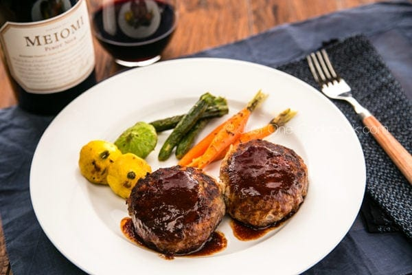 Hamburger Steak with grilled vegetable on the white plate and bottle of wine and glass.