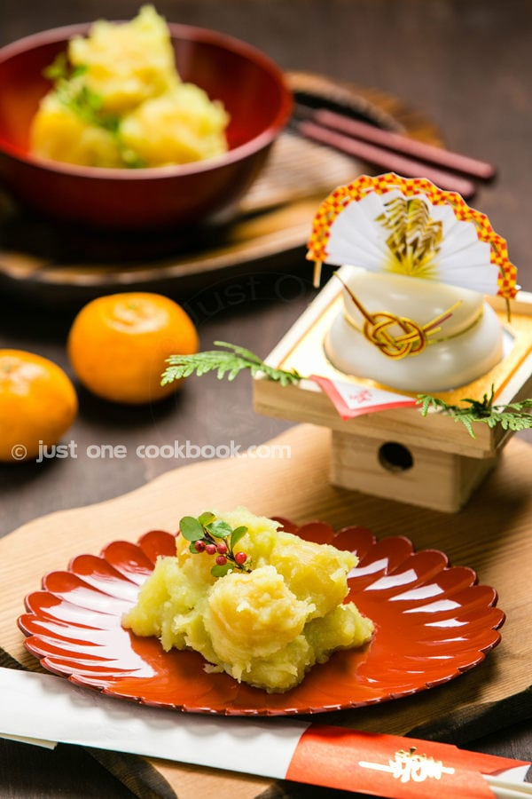 Kuri Kinton, Candied Chestnuts with Sweet Potatoes on a plate and Japanese's new year decoration on a table.
