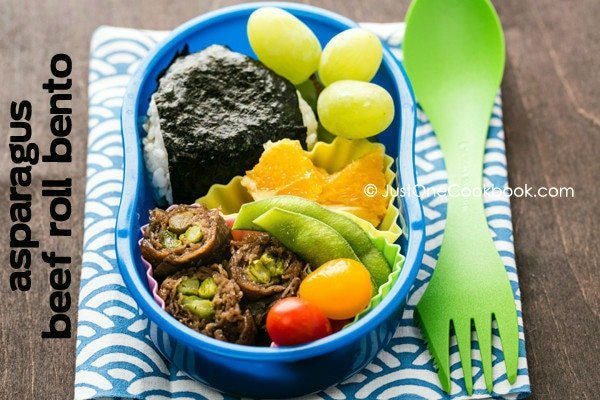 Asparagus Beef Roll Bento with onigiri, edamame, tomato and fresh fruit.