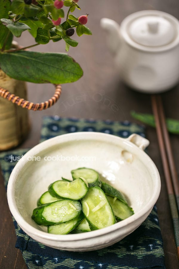 Pickled Cucumbers in a white bowl on a table.