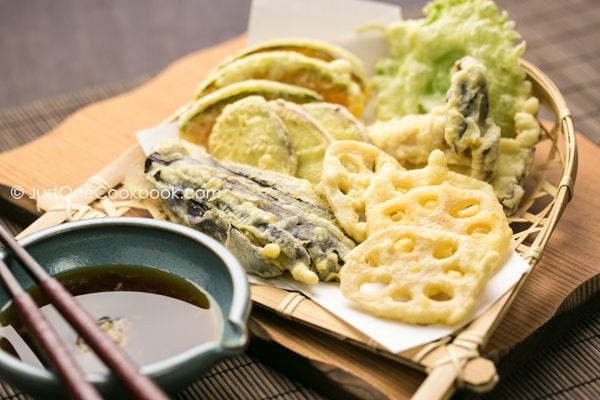 Vegetable Tempura in a bamboo basket and sauce in a small bowl.