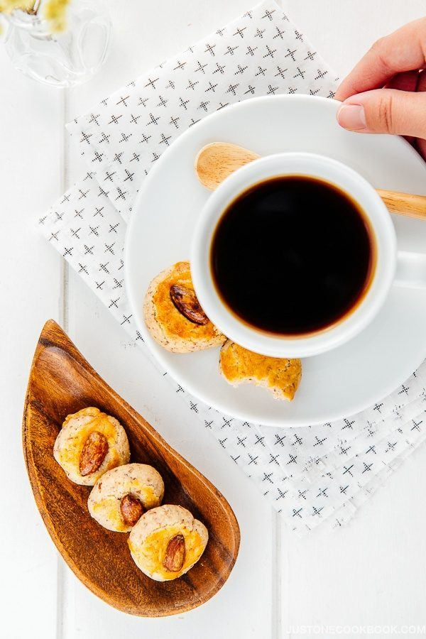 Chinese Almond Cookies on a wooden plate and a cup of coffee.