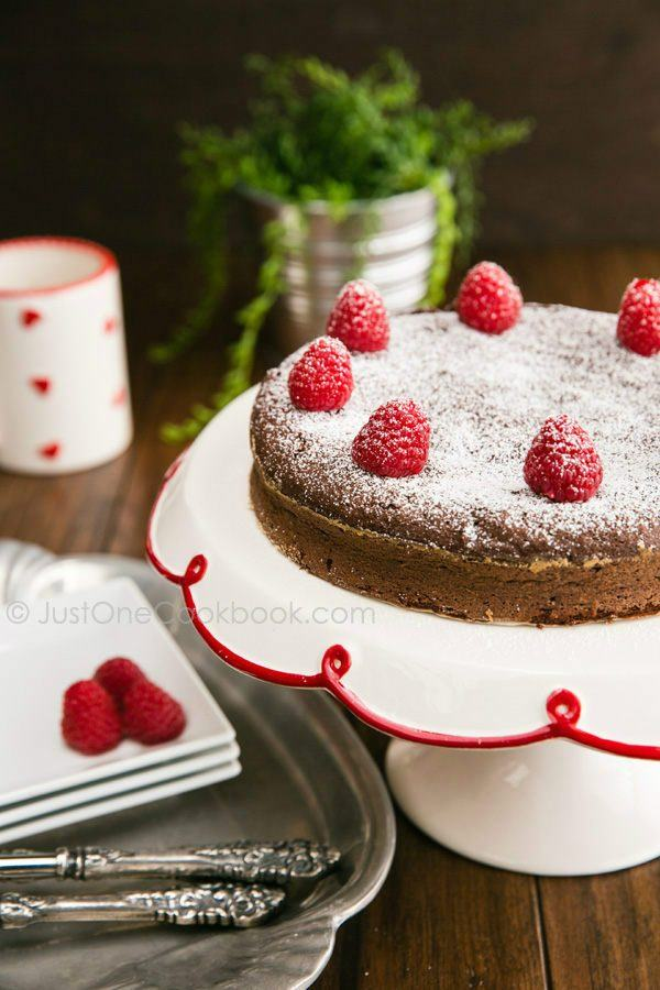 Chocolate Gateau with fresh raspberries and powdered sugar on top.