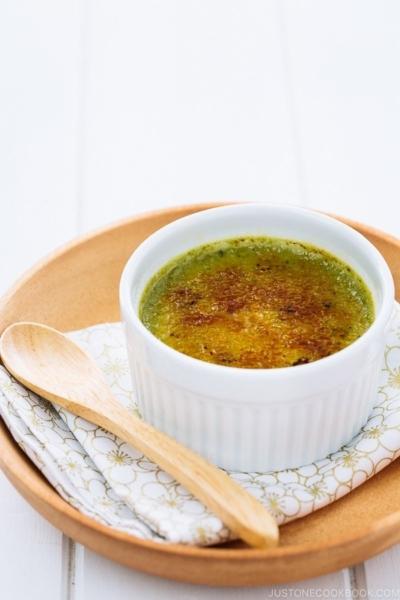 Green tea creme brulee in a white ramekin.