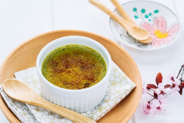 Green tea creme brulee in a white ramekin.