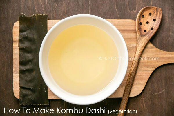 Kombu Dashi in the white bowl and Kombu on the wooden table.