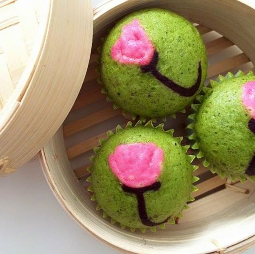 Green tea steamed cakes in a bamboo basket.