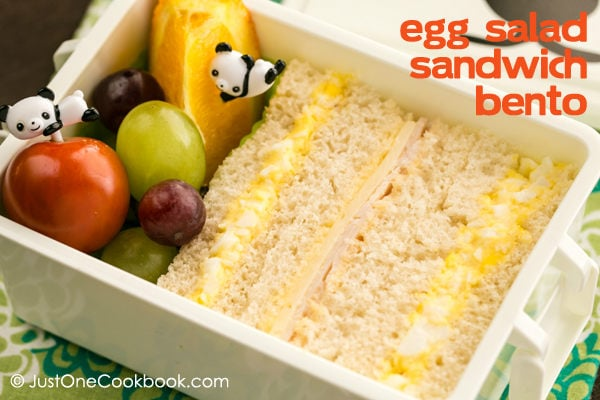 Egg Salad Sandwich Bento with fruits on a table.