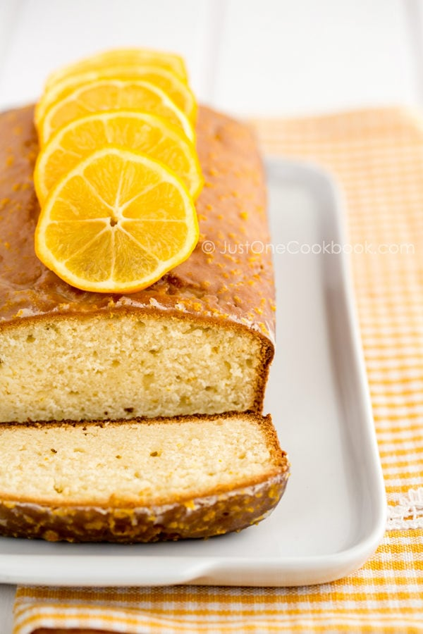 Meyer Lemon Pound Cake topped with sliced lemons on a white dish.