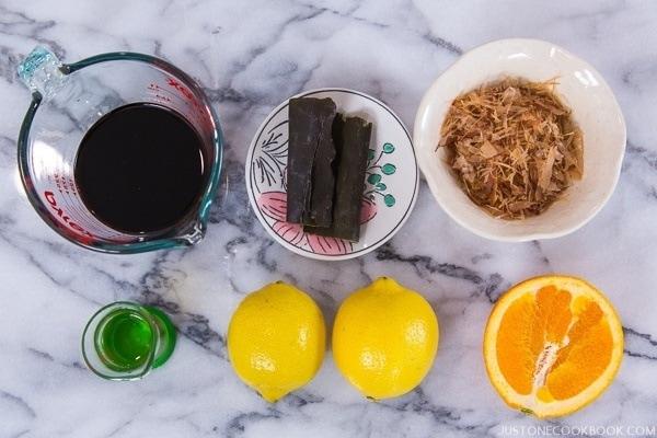 Ponzu Sauce Ingredients containing kombu, lemon, bonito flakes, mirin, and soy sauce.