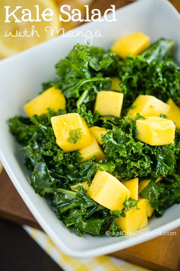 Massaged Kale Salad with Mango in a white dish.