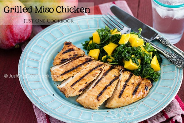 Grilled Miso Chicken with Kale salad with mango on a plate.
